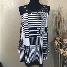 Black and White Geometrical Top Geo print top, silver tone grommets at neckline and a liquid fabric is perfect for the season. Throw on black or white capris, Strappy sandals, black bag and you are set for the day in style. NWT Cocomo Tops