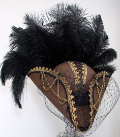 Tan Tricorn with gold and black trim, corset with either black or brass chains and fleur de lis and guipure lace band, chained sides, Merry Widow adjustable face veil, black drop beads, rear ornament plate and a full clutch of black ostrich feathers