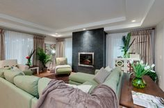 The Carleton - Living Room.  Large tiled floor to ceiling fireplace with a double tray ceiling.  Lots of space for entertaining.  www.qualityhomes.ca