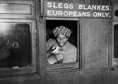 Unidentified woman ignoring seat restrictions in a train carriage to protest against Apartheid in South Africa, 1952 Still looking for photo credit
