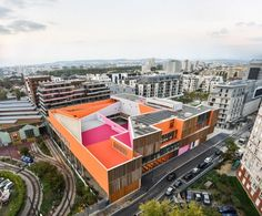 The Groupe Scolaire Simone Veil building hosts a 12-classroom primary school and a nine-room nursery, alongside a shared canteen, library and bright orange sports hall.