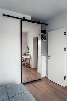 Minimalist interior of a bedroom with sliding doors . Verspiegelte Schi… Minimalist interior of a bedroom with sliding doors. Mirrored sliding doors cover the dresser and make-up table. Bedroom Divider, Closet Bedroom, Home Bedroom, Modern Bedroom, Room Divider Doors, Bedroom Decor, Interior Minimalista, Awesome Bedrooms, Interior Barn Doors