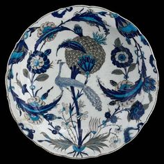 "Peacock dish. Turkey, ""Iznik"", c. 1550. This dish offers the viewer a complex vegetal composition combining elements from the saz repertoire – long serrated leaves, composite flowers and buds – with a more naturalistic style of plant motif – artichoke stems in bloom, flowers with swirling petals, tulips, and perhaps delicate violets. In the center is an errant peacock, lost in this fantastic garden."