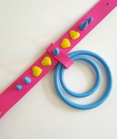 Neon Pink painted Genuine Leather choker, with Bright Yellow heart rivets, and Bright-Sky-Blue powder coated metal hardware. The largest O ring is 3 inches. The strap is 1 inch wide. Since the O ring is so big, it might be a bit heavy if youre not used to large hardware. But its very comfortable.  Fits 12-16.5 inch necks  Please allow me 3-5 days to ship it out!  Follow my Instagram @tumorcrunch for new items, shop updates, discounts, and giveaways