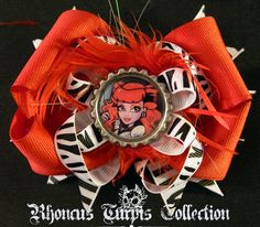 """have hand crafted, hand sewn this hair bow with one of my favorite Monster High dolls- Operetta- in mind! There are """"spikes"""" and loopy loops of zebra print on a beautiful bright red bow, Miss Operetta has been sealed in a silver bottle cap and secured to the center of the bow with red feathers surrounding her! This adorable design measures approx 4.5 x 3.75"""" and attaches in hair with an alligator clip. All ends have been heat sealed to prevent fraying."""