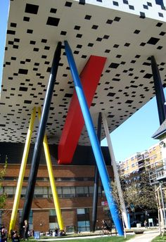 """The Sharp Centre for Design, 100 McCaul Street, is a fine example of how to expand a college campus without obliterating older buildings and disrupting classes. The Centre is part of the Ontario College of Art and Design – which inhabits a postage stamp sized piece of land downtown. English architect Will Alsop developed the brilliant idea of installing a rectangular 2-storey """"box"""", atop coloured, 26 metre tall columns. The """"box"""" contains art studios, lecture theatre and exhibition spaces"""