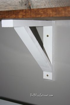 White DIY shelf bracket installed onto gray wall