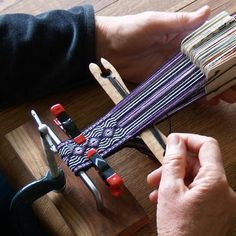 Simple Loom for Card Weaving--then she just hangs a weight (bag of rocks or a big plastic water bottle) on the bundle of warp ends - hanging over a chair at the  other end of the table!  From Gudrun Polak's weaving (and braiding) website The Loomy Bin