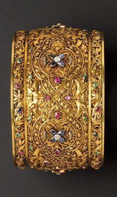 Renaissance Revival 18kt Gold Gem-set Armlet, c. 1880, the chased and engraved grillework form with foliate devices and strapwork, bezel-set with sapphire and diamond florets, bezel-set sapphire, emerald, and ruby accents, rose-cut diamond highlights.