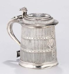 """A QUEEN ANNE SILVER TANKARD,  MARK OF JOHN RUSLEN, LONDON, 1707,  Later decorated with vertical fluting separated by wavy-edged, matted, horizontal bands, Onslow scroll thumbpiece and vacant rococo cartouche, handle with engraved contemporary initials, """"H"""" over """"IS"""", 7 in. high (17 cm.), 26 oz."""