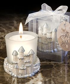 """Frankly, these elegant castle candle favors are a little enchanting. When your love is fit for a queen and king and your big day is straight from a storybook, you need these """"Once Upon a Time"""" candle favors to lend their fine detailing as the perfect finishing touch. Each castle candle measures two inches square and includes a frosted white votive holder that contains a poured white candle. These favors come ready for gifting in a silver-bottomed clear box trimmed with a white organza bow."""