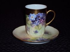 Beautiful hand painted Limoges Chocolate Pot with 6 cups and saucers. Decorated with purple pansies, handles and rims are gold. Pot is approx. 12 inches tall with lid and 5 inches wide at the base. P