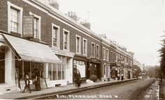 """Pembridge Road - """"Look past the boy looking at the camera and the woman in short sleeves. Can you see the sign: """"Best prices paid for old artificial teeth"""" Dentistry was a growth business in this period. Victorian London, Vintage London, Old London, West London, London History, Local History, British History, Old Pictures, Old Photos"""