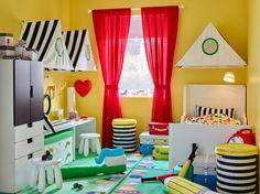 Fargerikt barnerom med sirkustema og gule vegger, røde gardiner og ei hvit uttrekkbar seng.