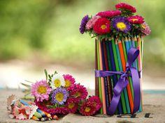 Colocar una banda elástica  por el medio en un florero de vidrio o en cualquier recipiente cilíndrico de plástico.  En el medio de la banda elástica, sujetar los lápices. Es posible usar lápices usados y de diferentes alturas.  Sacar la punta para que el trabajo quede organizado.  Tapar la banda elástica con una cinta de raso y elegir flores coloridas para completar el arreglo.