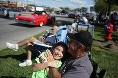 Families gather in the Woodward Median to watch the classic autos stroll by