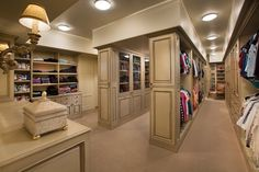 The sheer size of this closet is taken advantage of by putting another aisle into the room, providing an additional four walls of space and eight more cabinets. Glass-faced cabinets make another appearance in this room.