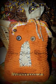 """Primitive Fall Chenille Pumpkin   His smile is a cinnamon stick, he has a burlap nose and big button eyes! All sewed on with black embroidery floss. His stem is made from burlap and he's topped off with a grunged cloth homespun leaf.  He is decorated with a tie at his stem of grunged cloth and twine and a rusty bell and safety pin.   He comes with a rusty wire for hanging on your door or you can also enjoy him indoors as well.   His overall height is 14"""", not including wire hanger."""