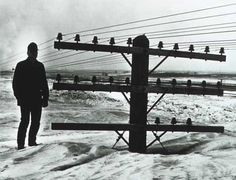 A man stands near a utility pole in North Dakota, March 9, 1966.  A spring blizzard produced snow so deep that it nearly buried the utility poles.