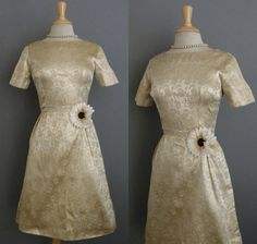 Ravishing gold dress in a rose patterned brocade. Gold metallic thread. Short sleeve fitted bodice. Nipped pleated waist. Flared skirt. Lined. Back metal zipper