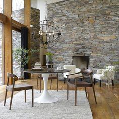 Une salle à manger avec une table ronde, une suspensions déco à la forme originale et un mur en pierres grises