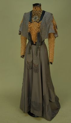 TRAINED WOOL AFTERNOON DRESS, EARLY 1900's. Pale blue 1-piece, the high neck lappet bodice with fringe and soutache having dotted net insert and sleeve beneath a shaped wool cape, cream lace insertion and embroidery, back hook & eye closures, skirt has deep swag applique with soutache.