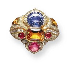 A FINE PADPARASCHAH SAPPIRE, GEM-SET AND DIAMOND BROOCH, BY BULGARI   Of bombé shield-shaped design, centering upon an octagonal-cut topaz weighing approximately 20.45 carats, flanked by oval-cut rubies, further enhanced by an oval-cut blue sapphire, weighing approximately 32.65 carats, and an oval-cut orange-pink Padparadschah sapphire weighing approximately 7.82 carats, accented by baguette and pavé-set diamonds, and buff-top calibré-cut citrines, mounted in 18K gold  Signed Bulgari