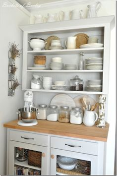 Baking station via Buckets of Burlap. I like the posts that look as if they're holding the cabinet up, the open shelving with beautiful dishes and the chicken wire in the cabinets below.