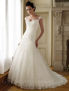 Allover lace and tulle A-line bridal gown features hand-beaded lace trimmed illusion cap sleeves. Lace modified sweetheart neckline. Directionally ruched bodice with asymmetrically dropped waistline and beaded lace appliqu