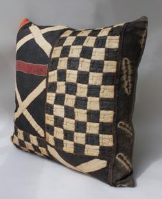 Kuba Cloth Pillow. This graphic pillow is handmade exclusively for Archeo from authentic Kuba textiles. Originally part of a ceremonial costume, each textile was handwoven from rafia fibers. With 100% down fill, these pillows are both luxurious and distinctive.