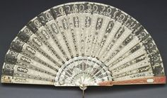 Queen Elizabeth's Faberge Fan. Creator:  Mikhail Evlampievich Perkhin (1860-1903) (workmaster) Creation Date:  c. 1900 Materials:  Cream silk and silk gauze leaf; front guard mother-of-pearl and two-colour gold enamelled in pink and white over a guilloché ground decorated with diamonds; sticks and back guard of pierced mother-of-pearl with silver piqué decoration (2 + 16); silver pin   Provenance:  Belonged to Queen Elizabeth The Queen Mother