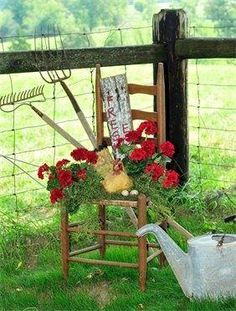 chair with geraniums, rakes, fence