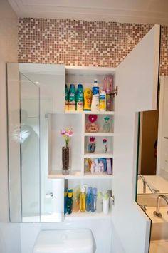 Recorte da porta do armário instalado sobre o vaso sanitário, quando fechada deixa a mostra o nicho central para expor decoração como a exemplo o vaso com flor.
