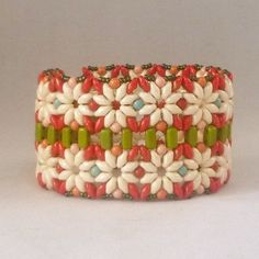 """""""Pickets"""" bracelet uses two types of these new two hole beads. The 'daisies' are created using Super Duo (or Twin) beads and the 'picket fence' is created with 2-hole Bricks. From Mikki Ferrugiaro on Artfire - pattern for purchase"""