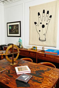 """Rashid Johnson and Sheree Hovsepian's home in W Magazine. A view of the library shows a taby by Johnson and his sculpture """"Black Steel in the Hour of Chaos,"""" 2010, and on the wall (from left) Ellen Gallagher's """"Abu Simbel,"""" 2005, and a hand tapestry by Mai-Thu Perret."""