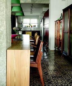 Azulejo hidráulico e cristaleiras antigas equilibram o ambiente com a coluna de cimento e a bancada em madeira clara.