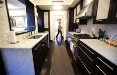 A woman walks past the kitchen in an apartment that is for sale for $4.5 million in New York January 13, 2011. . REUTERS/Lucas Jackson