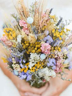 Use a little bit of everything like craspedia, delphiniums, lavender, and dried wheat for a standout wildflower wedding bouquet.