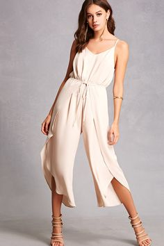A crepe woven jumpsuit featuring wide legs with a foldover layer on each leg that self-tie in the front offering a wrap-inspired design, a V-neckline, adjustable cami straps, back keyhole cutout with button closure, an elasticized waist, interior lining, and a flowy silhouette.<p>- This is an independent brand and not a Forever 21 branded item.</p>