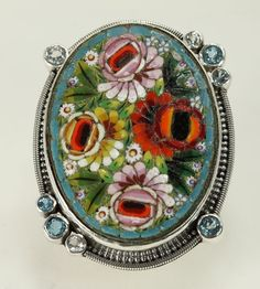 """This lovely and delicate micro-mosaic ring was hand-made in Italy in the late 19th century or early 20th century. The micro mosaic consists of very finely detailed ceramic or porcelain micro tiles that were placed by hand. The ring is set in heavy sterling silver and decorated with 4 blue topaz and 4 white topaz stones. The inside of the band bears the Mars & Valentine  logo.    1 7/8"""" long x 1 3/8"""" wide"""