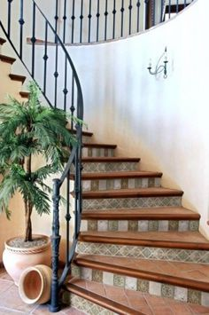 Tile staircase in a combination of wood, terracotta & neutral colored tiles on risers.