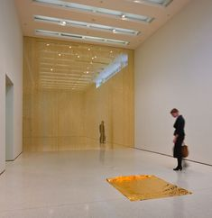 """Installation view of """"Paired, Gold: Félix González-Torres and Roni Horn,"""" 2010. Background: González-Torres, """"Untitled (Golden),"""" 1995. Curtain of Gold-Colored Plastic Beads. Foreground: Horn, """"Forms from the Gold Field,"""" c. 1980-82. Two-Pounds of Gold Compressed into Rectangular Sheet."""
