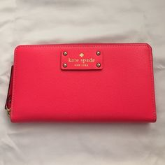 Kate spade neon pink wallet Kate spade neon pink wallet. Used once. 3rd picture shows a small dent on the front of the wallet (it came this way). Dent is not visible/noticeable unless you are right up close to it. 4th picture shows a different shade of pink passport holder (already sold) compared to wallet so color difference can be seen. kate spade Bags Wallets