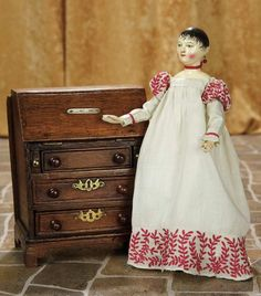 "12""-Very Rare and Fine Early Wooden Doll with Exquisite Painting and Carving~~~dowel jointing at shoulders, elbows, hips and knees, shapely lower legs with painted stockings and outlined yellow slippers. Comments: early 1800s, acquired by its present owner from an original English estate where it had resided for two centuries; included w/the doll is its original gown w/exquisite embroidery.~~~8 1/2-lid has  inscription containing name Theobold, circa 1820, English"