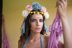 Tiara inpirada em Frida Kahlo feita de metal forrada com feltro e folhas de tecido, adornada com rosas de tecido, pedrarias, cordão de lã com pompons, contas douradas e fitas coloridas.