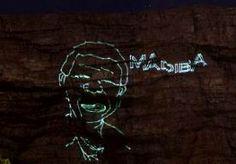"""10-Dec-2013 6:17 - MADIBA HERDACHT OP TAFELBERG. De Tafelberg bij Kaapstad is versierd met een gigantische afbeelding van Nelson Mandela. Met groene laserstralen werd als eerbetoon een afbeelding van de overleden oud-president geprojecteerd op de iconische berg. Naast zijn hoofd stond """"Madiba"""" geschreven. Dat is de bijnaam van Mandela. Normaal gesproken wordt de 1086-meter hoge berg alleen in de zomer verlicht. Dan zijn het schijnwerpers die de berg ook in het donker zichtbaar maken."""