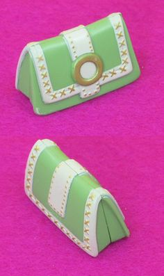 So fabulous! This little green clutch is super cute with white leatherette look trims, x stitching and gold buckle. Nice size! Bag is made of plastic and does not open.