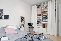 Create a floor to ceiling closet/storage area with shelving and curtains as doors