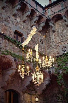 4 Chandeliers of of diffrent sizes and heights hang in an outdoor garden, just love!