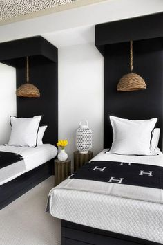Interior design ideas and tips to make sure you're guest room is always perfectly prepped and ready for visitors, just like this monochromatic black and white bedroom with matching twin beds, hanging woven wicker pendant lights, white shams with piped edging in black, patterned monogrammed throw blankets, DIY hanging canopies, wood nightstands between the beds and a cutout white lantern as a decorative accent.